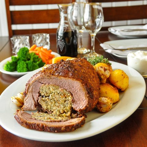 Smoked Paprika Lamb with Summer Savory Stuffing Square cropped featured image of carved lamb with side dishes