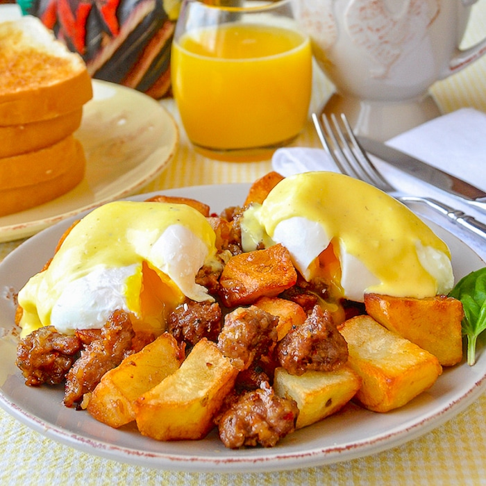 Italian Sausage Hash Eggs Benedict with Parmesan Hollandaise Sauce showing poached eggs broken open and runny