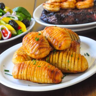 Garlic Concertina Potatoes a.k.a. Hasselback Potatoes shown with steak, salad and shrimp in the background