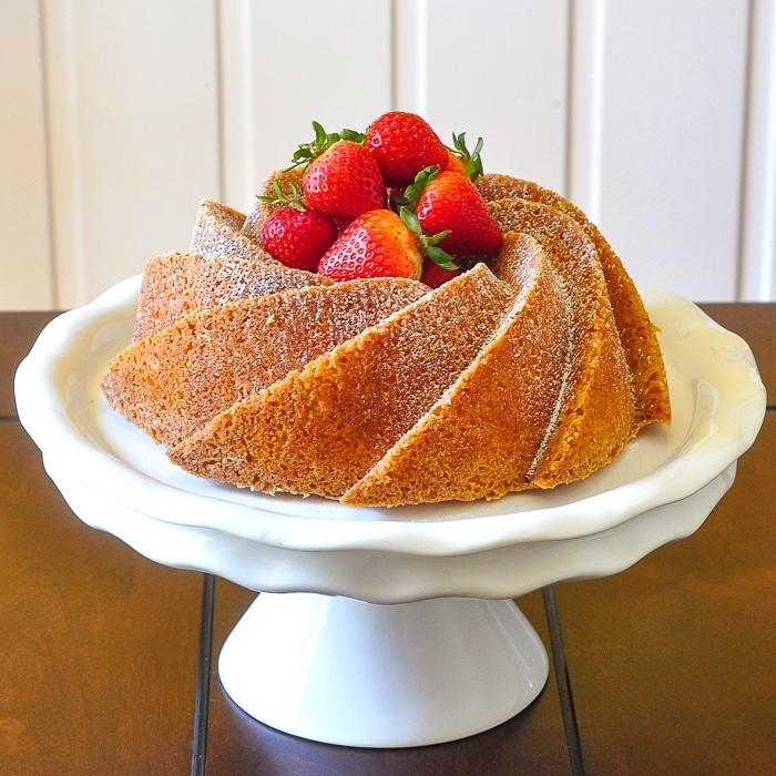 Orange Bundt Cake on a white pedestal stand