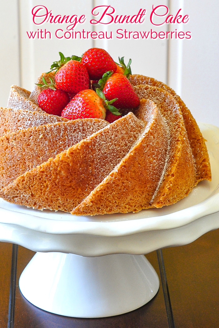 Orange Bundt Cake uncut on a white pedestal stand with title text added for Pinterest