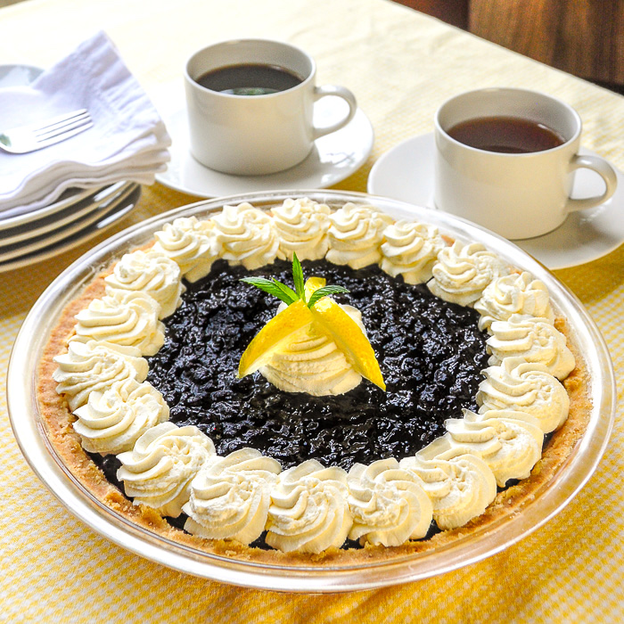Photo of completed Lemon Blueberry Cheesecake Pie with coffee in the background
