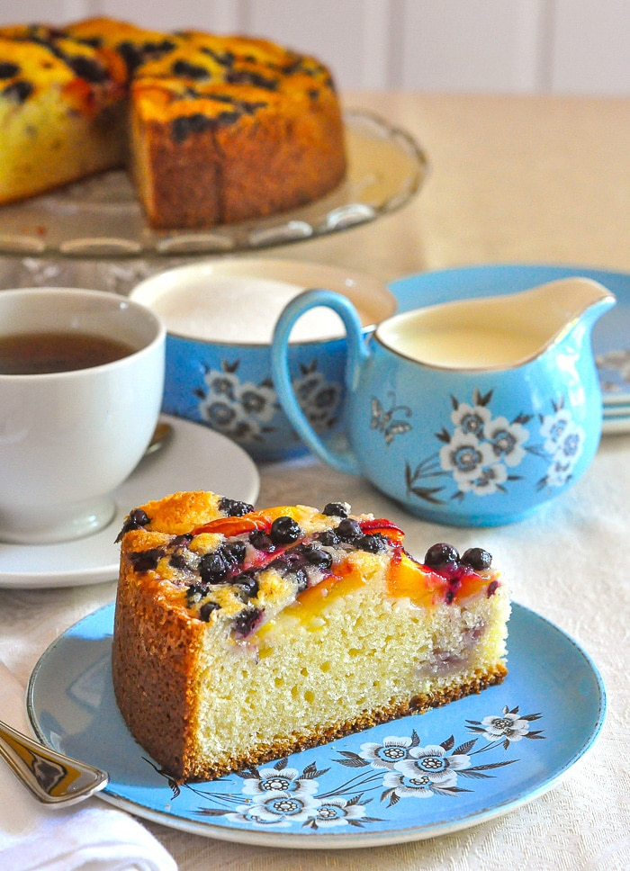 Blueberry Peach Sour Cream Cake photo of a slice and blue tea service with cake in the background.