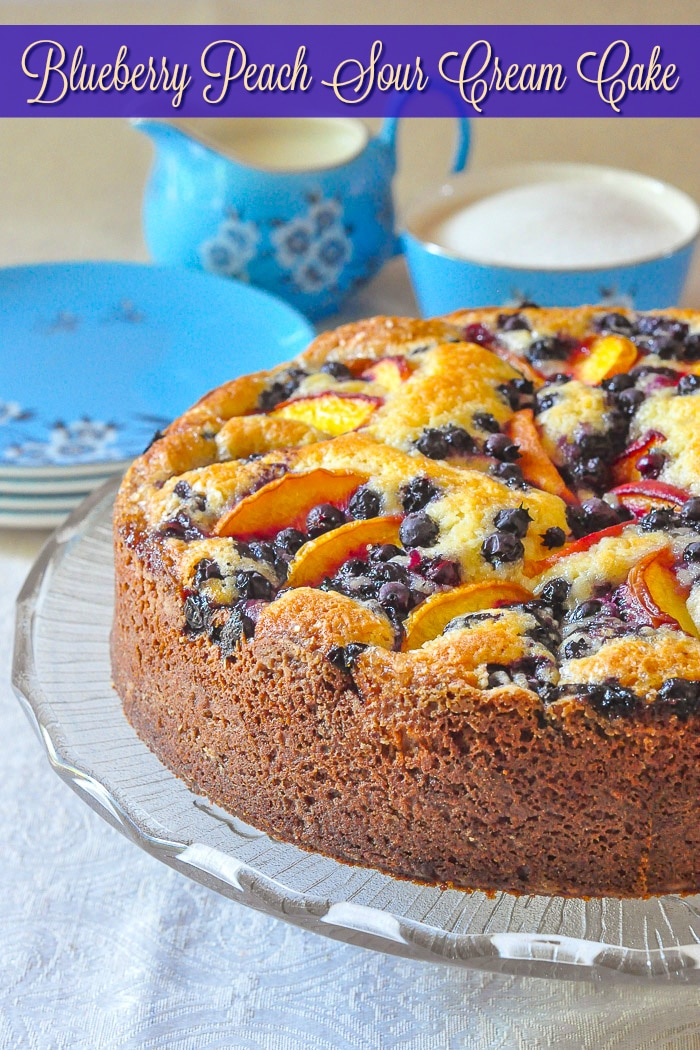 Blueberry Peach Sour Cream Cake photo of uncut cake with title text added for Pinterest