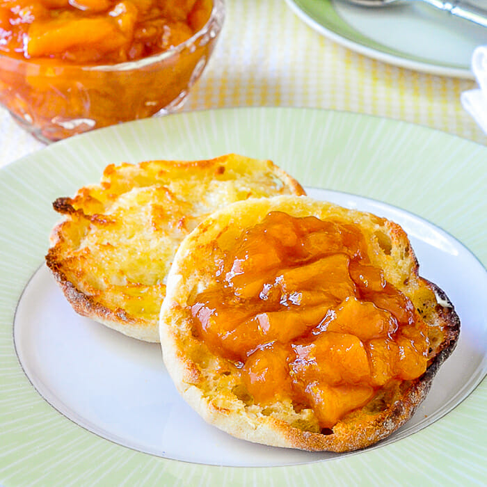 Easy Roasted Peach Jam shown on a toasted English muffin.