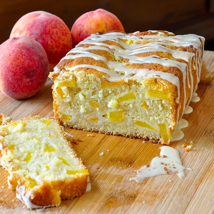 Peach Cake with Vanilla Glaze on a wooden cutting board