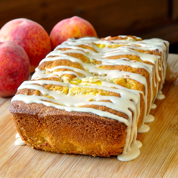Peach Cake with Vanilla Glaze uncut with peaches in the background