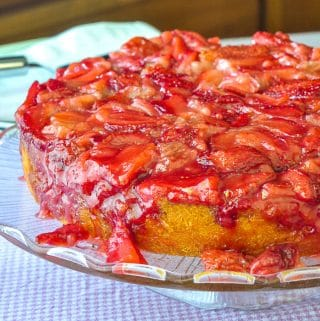 Strawberry Upside Down Cake photo of uncut cake on a clear glass cake pedestal