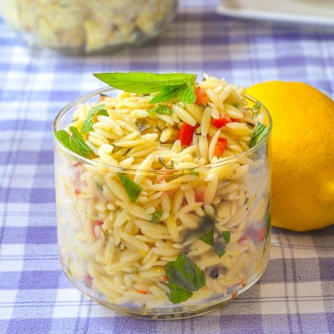 Lemon Mint Orzo Salad in a clear glass serving dish with a whole lemon on the side
