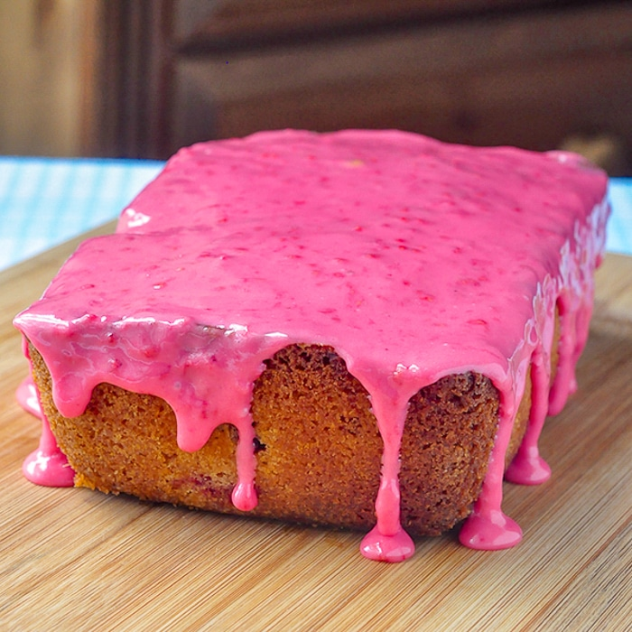 Raspberries and Cream Loaf Cake glazed uncut on a wooden cutting board