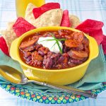 Smoked Sausage Chili in a yellow serving bowl with corn chips on the side