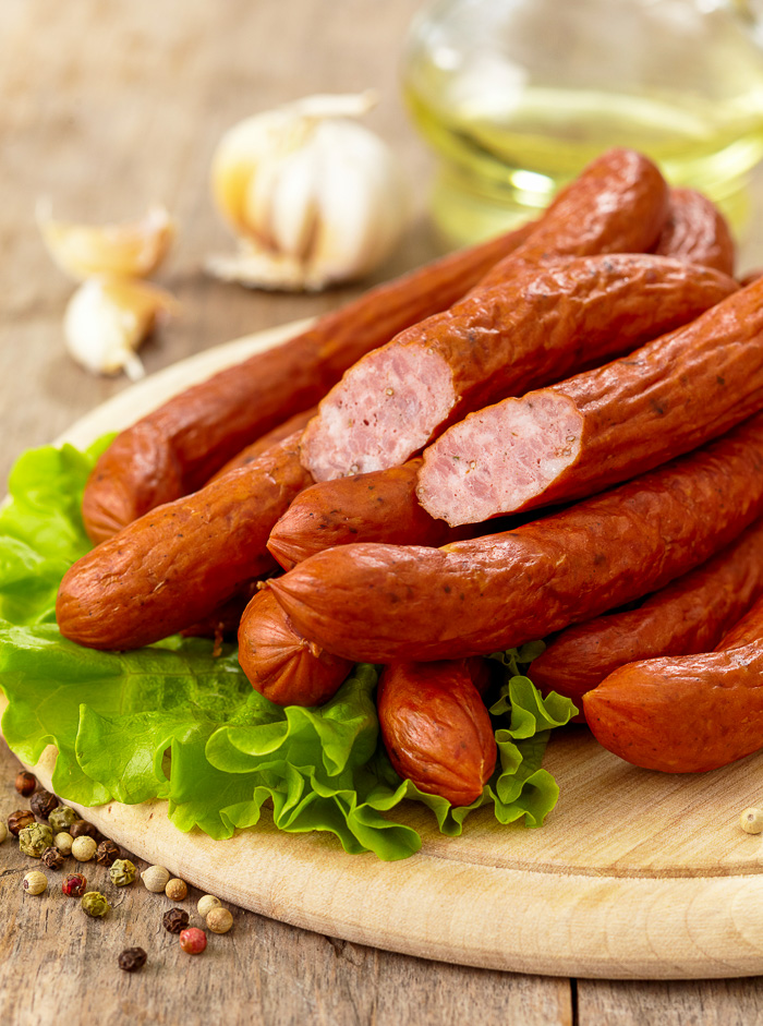 Stock photo of smoked sausages on a wooden cutting board.