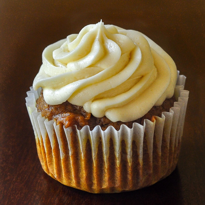 Sticky Toffee Pumpkin Cupcakes close up photo of a single cupcake on a dark wooden table