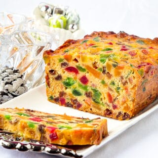Apricot Fruitcake shown on a white background with candles in background