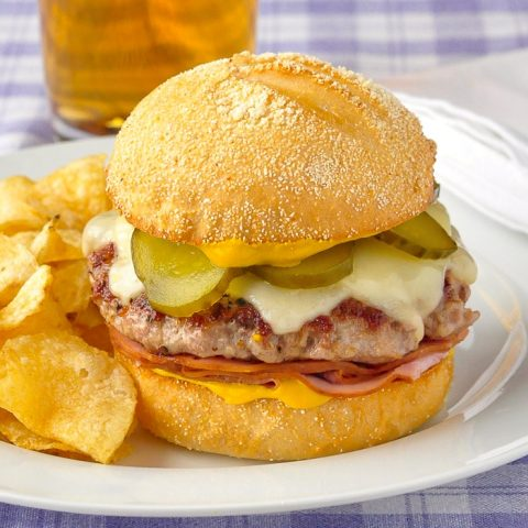 Cuban Sandwich Burger pictured with potato chips and beer