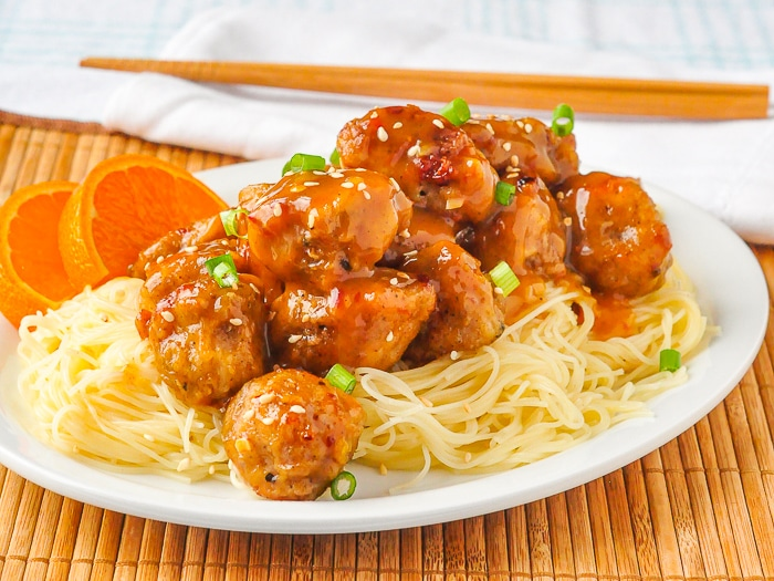 Orange Chicken on a white serving platter with chopsticks in the background