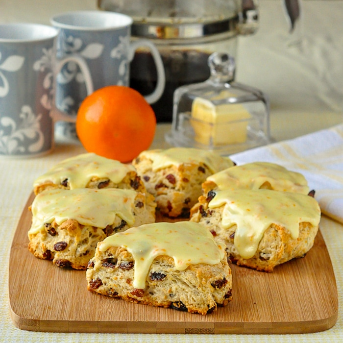 Orange Raisin Scones wide shot of scones on wooden board with coffee in background