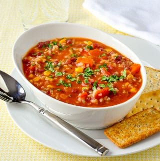 Dirty Rice and Beans Soup photo of a single serving in white bowl with crackers on the side