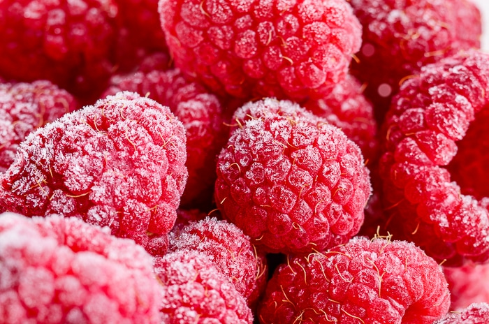 Red frozen raspberries background closeup photo