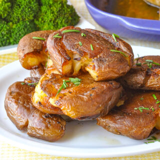 Smash Roasted Potatoes pictured stacked on a white plate