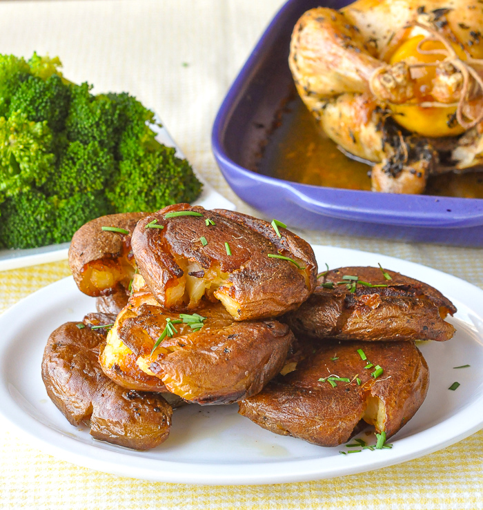 Smash Roasted Potatoes pictured with roast chicken and steamed broccoli in the background
