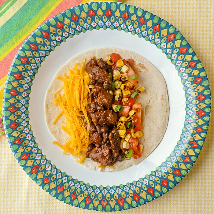Beef Tacos From the Slow Cooke single taco on multicoloured plate
