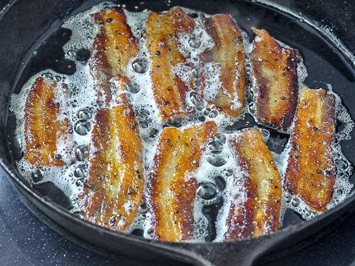 Homemade Bacon frying in cast iron pan