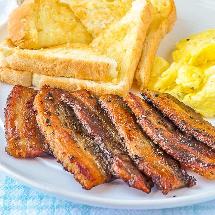 Homemade Bacon with eggs and toast on white plate