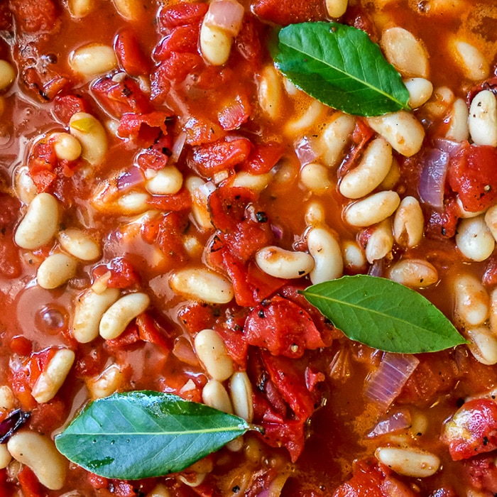 Chicken Braised in Fire Roasted Tomato Sauce photo of beans and tomatoes going into the pot