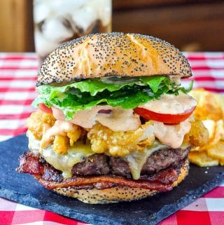 Completed Barbecue Spice Burger swith potato chips on a slate serving plate