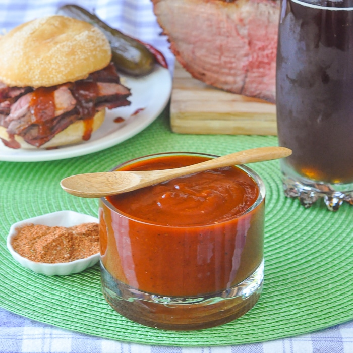 Smoky Spice Honey Barbecue Sauce in a clear glass container with small wooden spoon