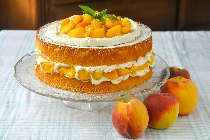 Bourbon Peach Shortcake photo of uncut cake with fresh peaches on the side
