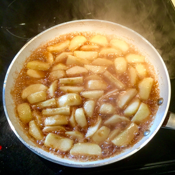 Apples cooking in a large saute pan.