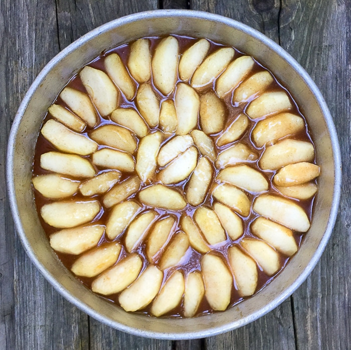 Arranging the apples in the bottom of the pan.