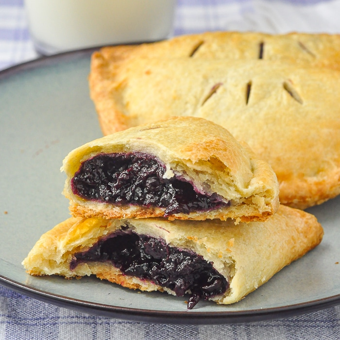Blueberry Turnovers on a blue plate with milk in the background