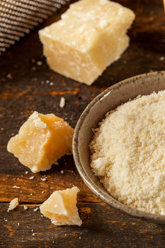 parmigiano reggiano shown in chunks and grated on a wooden background