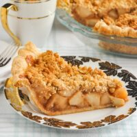Deep Dish Apple Crumble Pie featured photo of a slice of cake on a white and gold plate