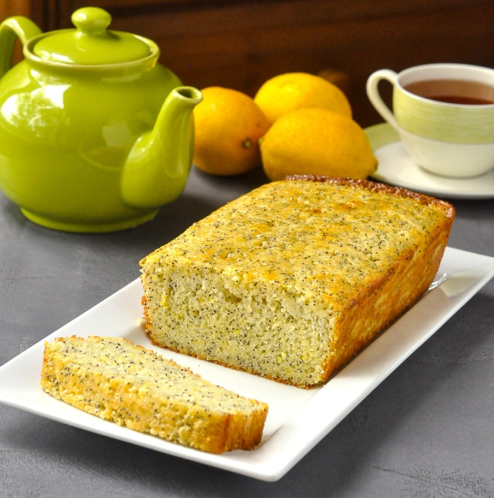Lemon Poppy Seed Loaf Cake on white serving platter with tea service and fresh lemons in background