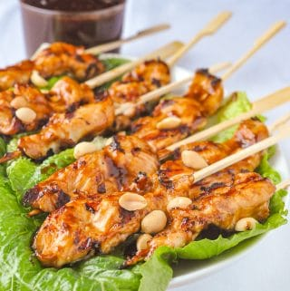 Peanut Butter Sriracha Chicken Satay on a bed of lettuce
