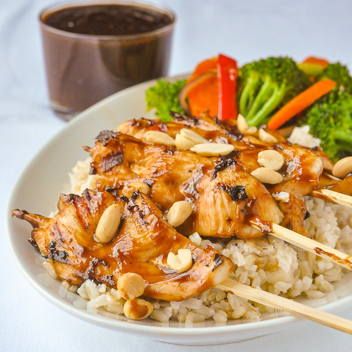 Peanut Butter Sriracha Chicken Satay served on a bed of rice with steamed vegetables