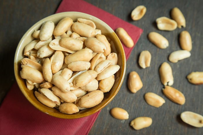 Roasted peeled peanuts in rustic bowl on wooden background (focus on peanut in bowl)