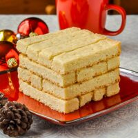 Scottish Shortbread stacked on a red plate surrounded by christmas decorations
