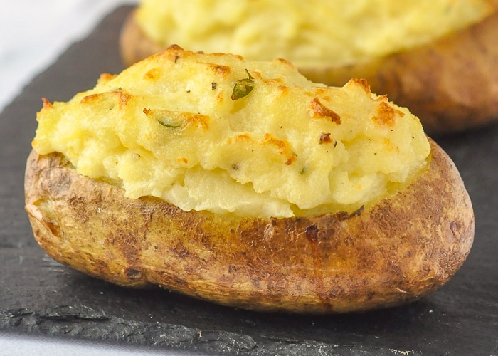 Twice Baked Potatoes with Smoked Cheddar & Thyme close up image of one potato on slate serving platter