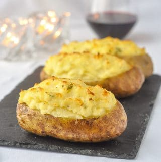 Twice Baked Potatoes with Smoked Cheddar & Thyme on a slate serving platter with wine and candles in background