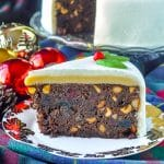 Ultimate Nut Fruitcake slioce on plate with gold leaf, Christmas tree ornaments in background.
