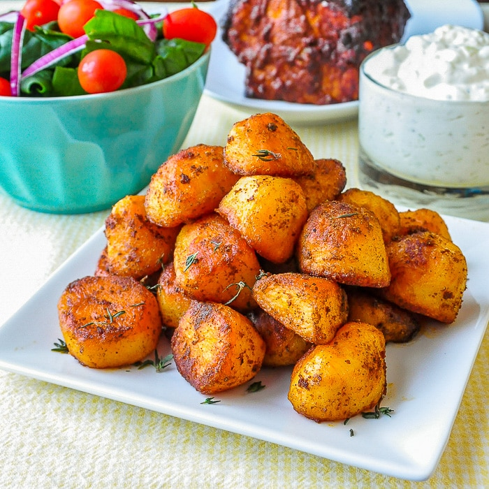 Smoked Paprika Roasted Potatoes wide shot on white serving platter with salad and tzatziki in the background