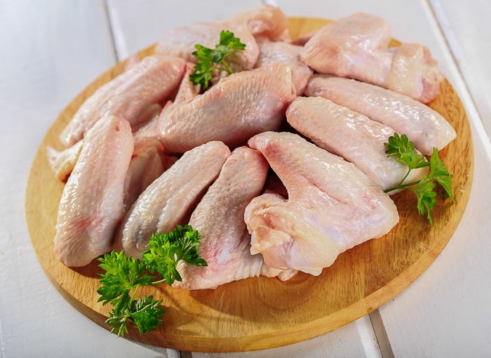 Stock photo of raw chicken wings on chopping board with parsley