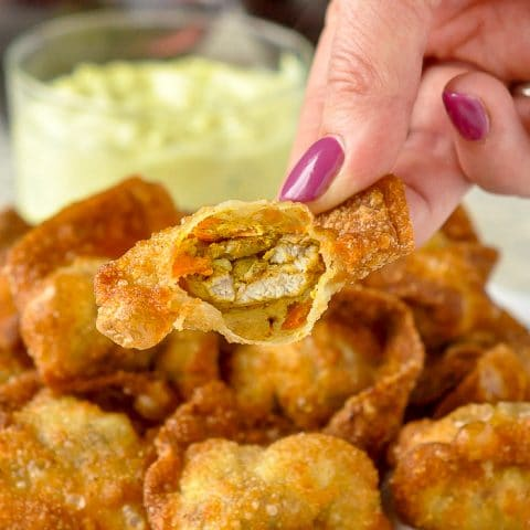 Curry Chicken Stuffed Wontons close up photo of one wonton broken open to reveal the curry chicken filling