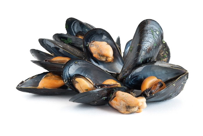group of mussels boiled with garlic and parsley isolated on white background