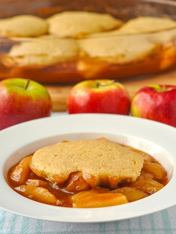 Apple cobbler photo of a single serving with apples and baking dish in background